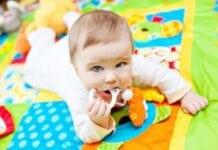 játszószőnyegen fekvő baba