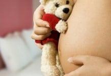 várandós kismama plüssmacit szorít a hasához