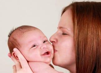 anyuka megpuszilja mosolygós babaját