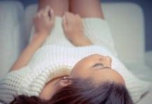 fiatal nő fehér pulóverben fekszik az ágyon