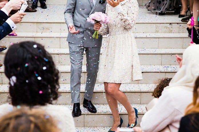 ifjú pár ra konfettit szórnak a templom lépcsőn