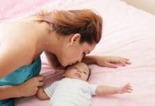 édesanya megpuszilja a kisbabája fejét