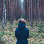 fiatal nő áll az erdőben