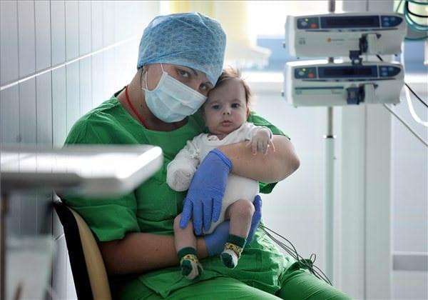 A három hónapos Farkas Richárd ül édesanyja karjában. MTI Fotó: Kovács Tamás