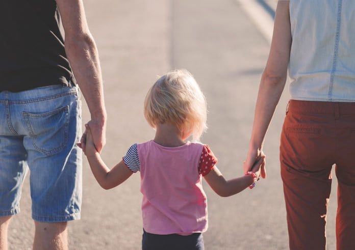 kislány a szülei kezét fogja az utcán