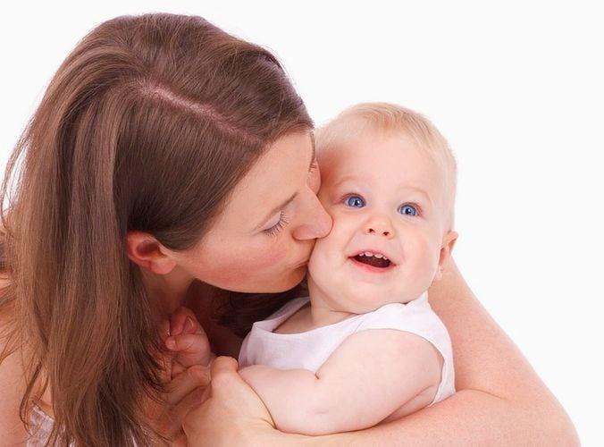 anya megpuszilja a babáját