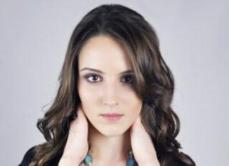 fiatal barna szemű nő fogja a nyakát