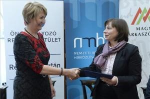 Fazekas Ildikó, az Önszabályozó Reklámtestület főtitkára átadja Karas Monikának, az NMHH elnökének az aláírt dokumentumot. MTI Fotó: Soós Lajos