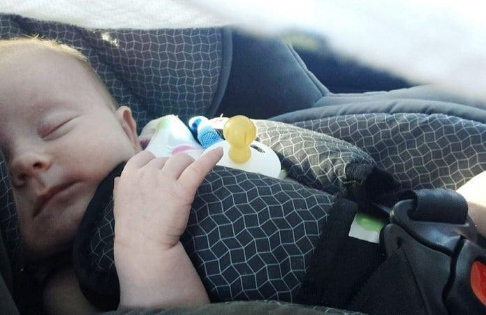 pici baba alszik az autóülésben bekötve