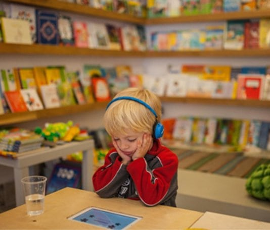 könyvtárban fejhallgatóval mesét hallgató kisfiú
