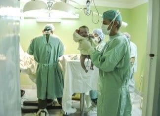 újszülött a szülész orvos kezében a műtőben