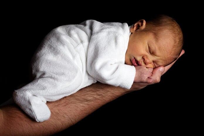 újszülött az apukája alkarján fekszik