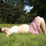 várandós kismama fekszik a fűben nyári ruhában