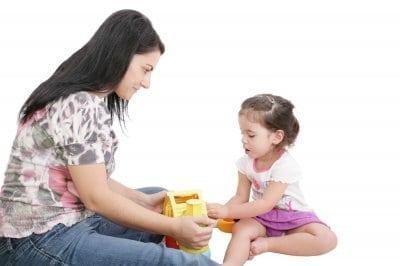 fiatal nő játszik egy kislánnyal