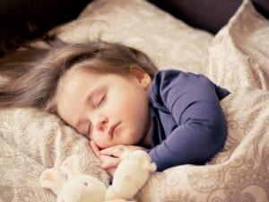 kislány alszik az ágyban egy plüssállattal