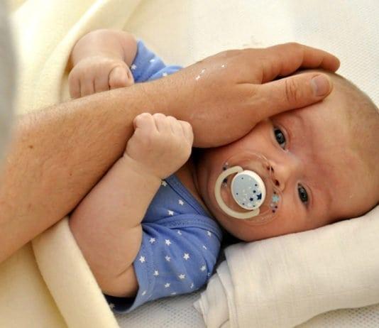 férfi kéz kisbabát simogat