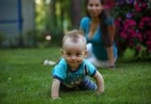 kisbaba a fűben négykézláb mászik