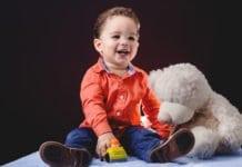 kisfiú ül a játékaival é s beszél