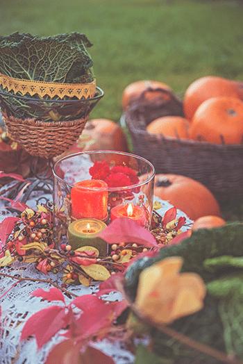 őszi kertben megterített asztal tökökkel, gyertyával