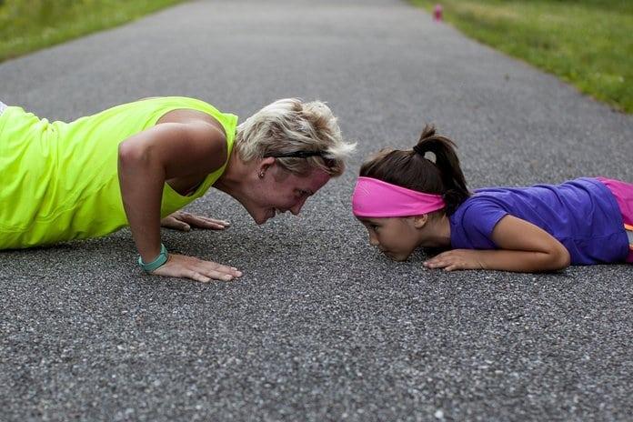 anya lánya sportos ruhában fekvőtámaszt csinál a betonon