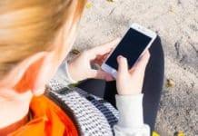 nő kezében tart egy mobiltelelfontt