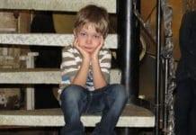 kisfiú unatkozva ül a lépcsőn