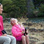 anya és lánya ülnek egy kövön távcsővel